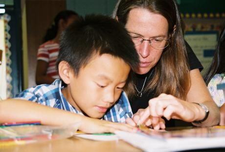 Associate Professor Rebecca Ambrose works with an elementary school student on solving a math problem.
