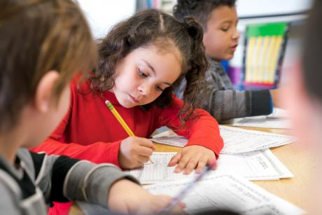 Young girl wearing red sweater holds a pencil while concentrating on worksheet in classroom