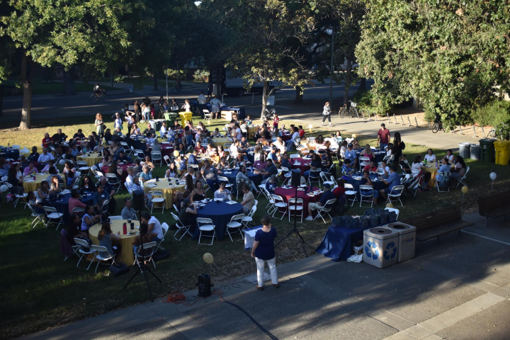 Aerial shot of large group of people sitting at tables outside