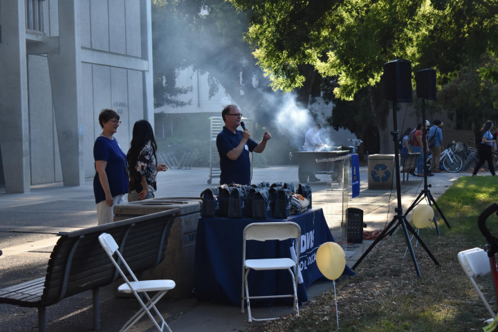 People speak at microphone with BBQ behind them