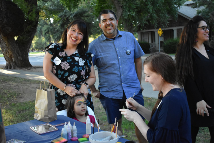 Elizabeth Montaño and Danny Martinez pose for camera as child gets face painted