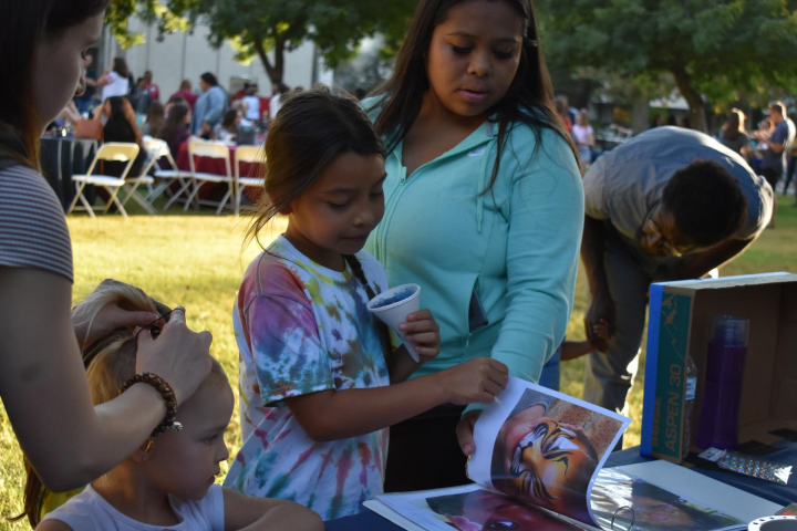 Children look through book of face painting options