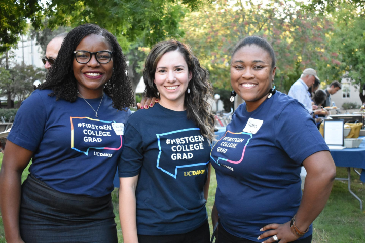 "Three women wearing ""FirstGen College Grad"" t-shirts pose together"