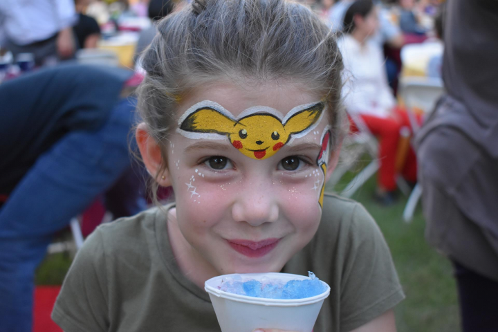 Child with Pikachu face painting eats ice dessert