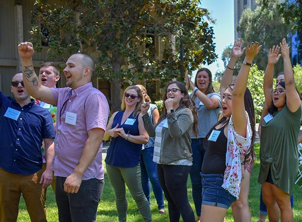 Group of teaching credential students cheer as they watch a game of rock-paper-scissors on a grassy lawn