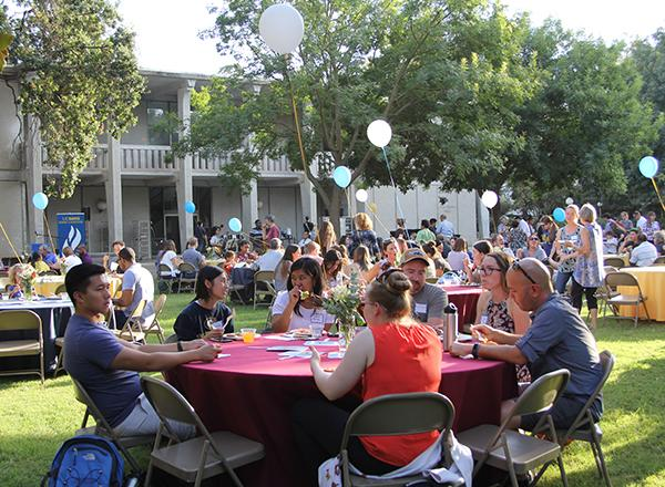 People sit at round tables with balloons during Fall Welcome event