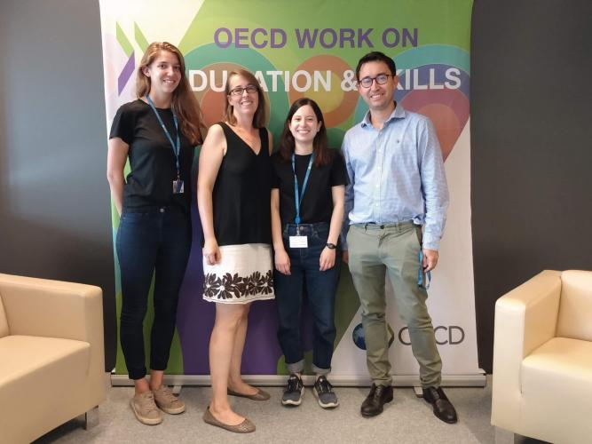 Megan Welsh poses with other researchers in front of an OECD banner