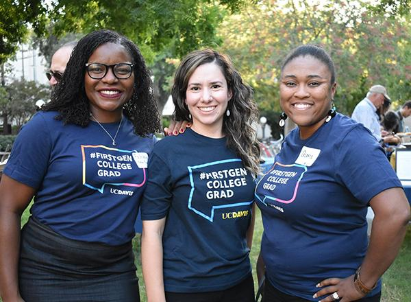 "Three women standing together wearing ""#FirstGen College Grad"" t-shirts"